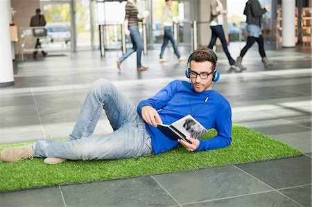 Businessman listening to music and reading book while relaxing on grass mat in an office lobby Stock Photo - Premium Royalty-Free, Code: 6108-06168275