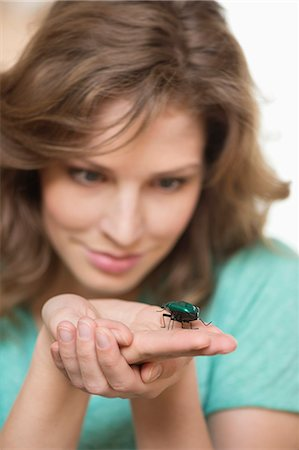 Woman looking at a beetle on her hands Stock Photo - Premium Royalty-Free, Code: 6108-06168365