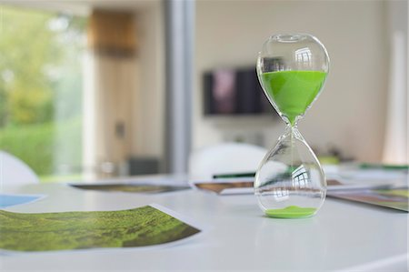poster - Green hourglass and ecological poster on a table Stock Photo - Premium Royalty-Free, Code: 6108-06168373
