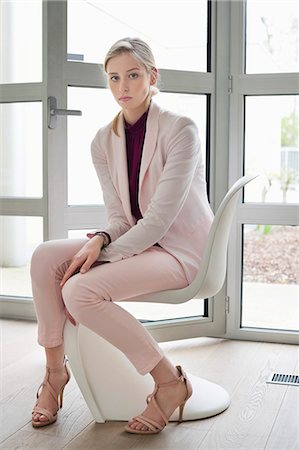 Businesswoman sitting on a chair Stock Photo - Premium Royalty-Free, Code: 6108-06168377
