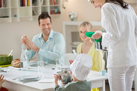Little boy assisting his mother in serving dinner Stock Photo - Premium Royalty-Free, Code: 6108-06168386