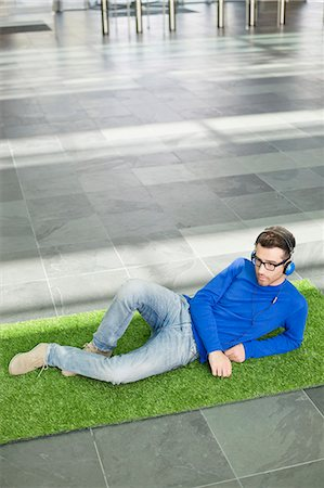 Businessman relaxing on grass and listening to music in an office lobby Stock Photo - Premium Royalty-Free, Code: 6108-06168335
