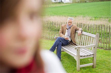 farm phone - Close-up of a girl with her father text messaging in the background Stock Photo - Premium Royalty-Free, Code: 6108-06168482