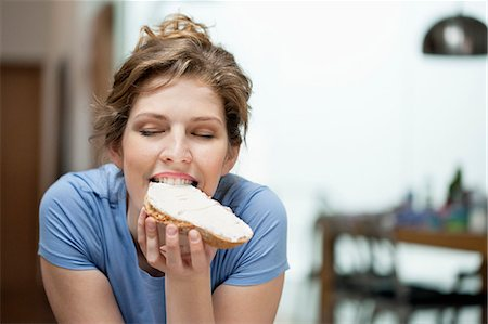 eating - Close-up of a woman eating toast with cream spread on it Stock Photo - Premium Royalty-Free, Code: 6108-06168410