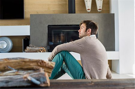 sweater and fireplace - Man sitting in front of a fireplace at home Stock Photo - Premium Royalty-Free, Code: 6108-06904541