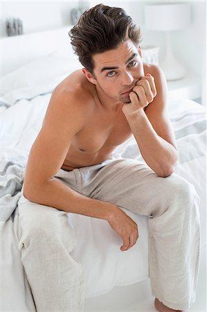 shirtless men - Serious man sitting on the bed Stock Photo - Premium Royalty-Free, Code: 6108-06904566