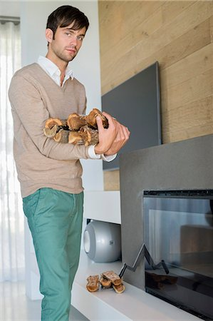 sweater and fireplace - Portrait of a man carrying firewood Stock Photo - Premium Royalty-Free, Code: 6108-06904574