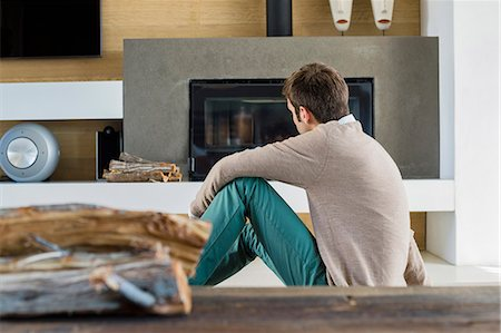 sweater and fireplace - Man sitting in front of a fireplace at home Stock Photo - Premium Royalty-Free, Code: 6108-06904579