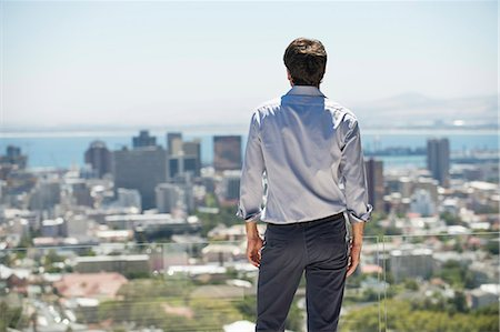 Man standing on the terrace looking at a city Stock Photo - Premium Royalty-Free, Code: 6108-06904585