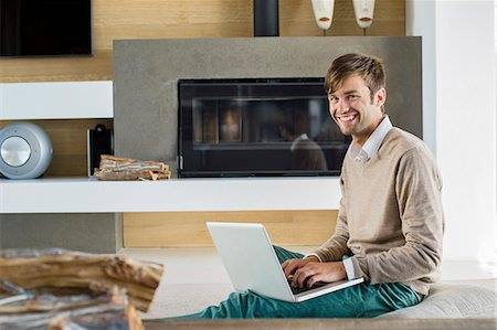 sweater and fireplace - Portrait of a smiling man using a laptop Stock Photo - Premium Royalty-Free, Code: 6108-06904588