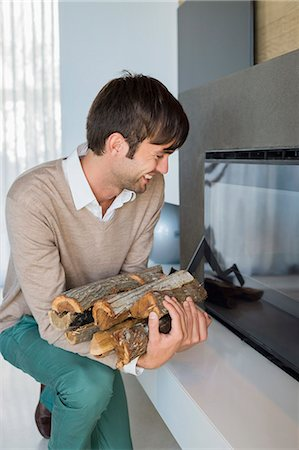 sweater and fireplace - Smiling man carrying firewood Stock Photo - Premium Royalty-Free, Code: 6108-06904589