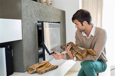 sweater and fireplace - Man putting firewood into a fireplace Stock Photo - Premium Royalty-Free, Code: 6108-06904536