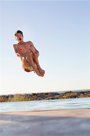 Man jumping into a swimming pool Stock Photo - Premium Royalty-Free, Code: 6108-06904661
