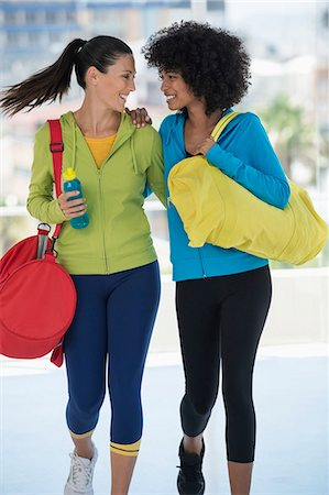 Two happy female friends carrying gym bags Stock Photo - Premium Royalty-Free, Code: 6108-06904622