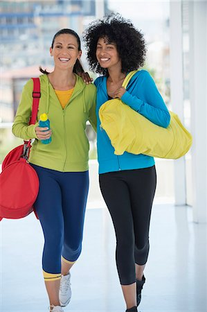 Two happy female friends carrying gym bags Stock Photo - Premium Royalty-Free, Code: 6108-06904629