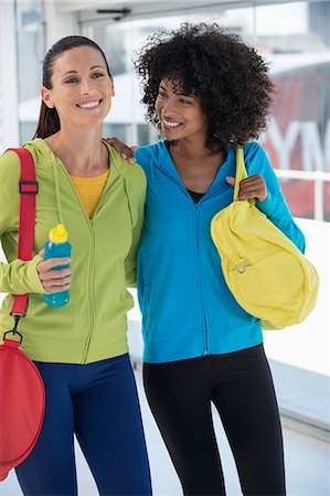 Two happy female friends carrying gym bags Stock Photo - Premium Royalty-Free, Code: 6108-06904631