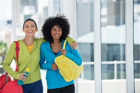 Two happy female friends carrying gym bags Stock Photo - Premium Royalty-Free, Code: 6108-06904635