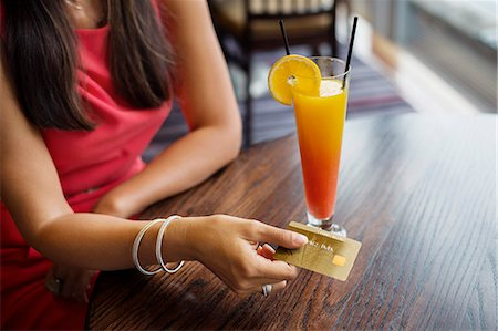 Woman paying with a credit card on a table in a restaurant Stock Photo - Premium Royalty-Free, Code: 6108-06904756