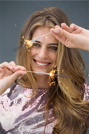 Woman celebrating with sparkler and smiling Stock Photo - Premium Royalty-Free, Code: 6108-06904759