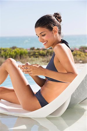 summer - Beautiful woman text messaging on a cell phone on the beach Stock Photo - Premium Royalty-Free, Code: 6108-06904705