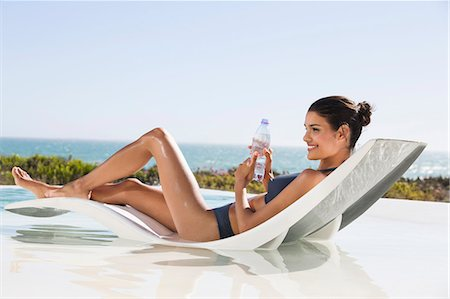 Beautiful woman holding a water bottle while sunbathing on the beach Stock Photo - Premium Royalty-Free, Code: 6108-06904711