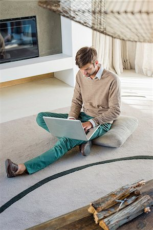 sweater and fireplace - Man using a laptop at home Stock Photo - Premium Royalty-Free, Code: 6108-06904858