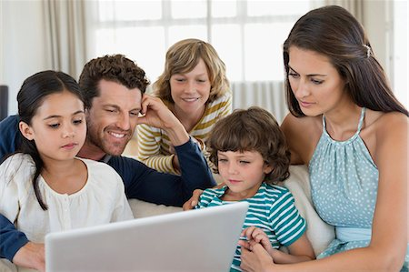 preteen long hair - Family looking at a laptop Stock Photo - Premium Royalty-Free, Code: 6108-06904863