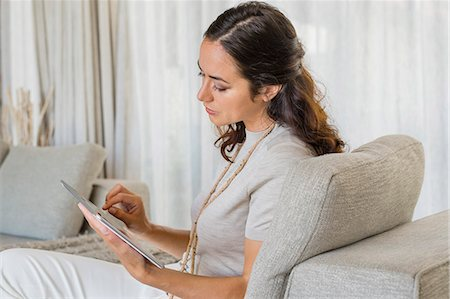 Beautiful woman using a digital tablet and smiling on a couch Stock Photo - Premium Royalty-Free, Code: 6108-06904881