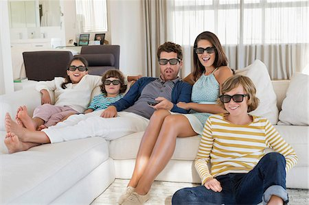 entertainment - Family watching television at home while wearing 3D glasses Stock Photo - Premium Royalty-Free, Code: 6108-06904899