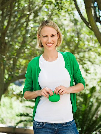 Smiling beautiful woman holding a pouch bag Stock Photo - Premium Royalty-Free, Code: 6108-06904801