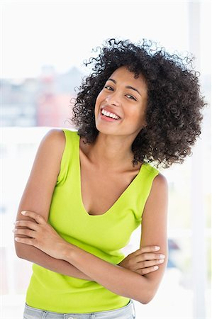 Woman standing with her arms crossed and smiling Stock Photo - Premium Royalty-Free, Code: 6108-06904806