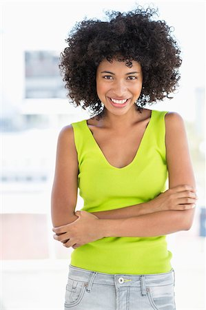Woman standing with her arms crossed and smiling Stock Photo - Premium Royalty-Free, Code: 6108-06904819