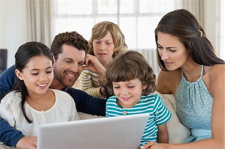 preteen long hair - Family looking at a laptop Stock Photo - Premium Royalty-Free, Code: 6108-06904829