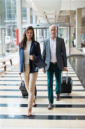 partnership - Business couple pulling suitcases in a hotel lobby Stock Photo - Premium Royalty-Free, Code: 6108-06904979