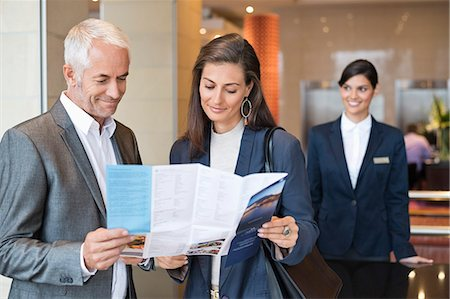 services - Business couple reading a brochure in front of a hotel reception counter Stock Photo - Premium Royalty-Free, Code: 6108-06904981