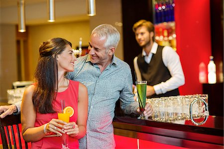 Couple enjoying drinks at the bar counter Stock Photo - Premium Royalty-Free, Code: 6108-06904982