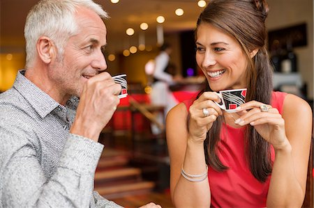 Couple enjoying cup of tea in a restaurant Stock Photo - Premium Royalty-Free, Code: 6108-06904987