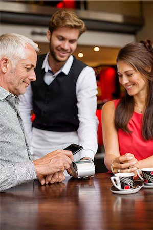 Waiter showing credit card reader to a couple on a table in a restaurant Stock Photo - Premium Royalty-Free, Code: 6108-06904988