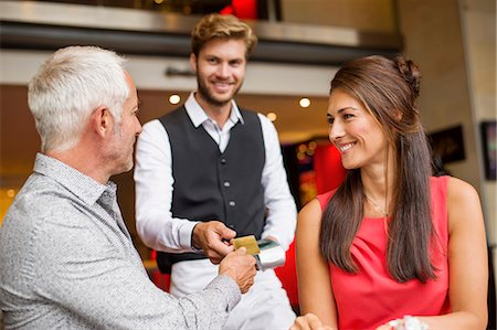 Couple paying with a credit card to a waiter in a restaurant Stock Photo - Premium Royalty-Free, Code: 6108-06904992