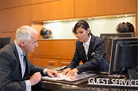 services - Receptionist showing a brochure to a businessman at a hotel reception counter Stock Photo - Premium Royalty-Free, Code: 6108-06904994