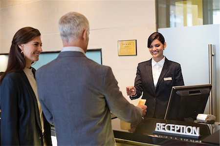 Business couple paying with a credit card at the hotel reception counter Stock Photo - Premium Royalty-Free, Code: 6108-06905043