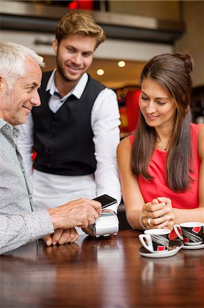 person on phone with credit card - Waiter showing credit card reader to a couple on a table in a restaurant Stock Photo - Premium Royalty-Free, Code: 6108-06905047