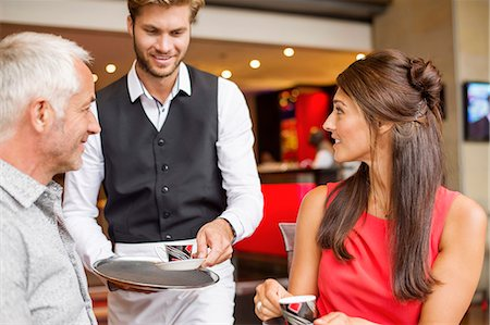 Waiter serving tea to a couple in a restaurant Stock Photo - Premium Royalty-Free, Code: 6108-06905052