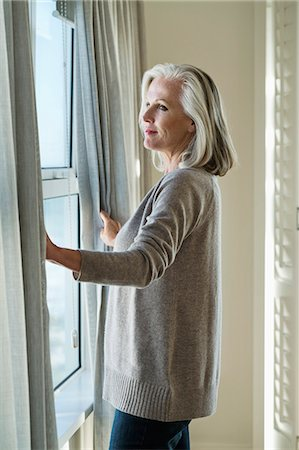 Woman standing by a window Stock Photo - Premium Royalty-Free, Code: 6108-06905080