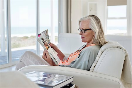 Woman sitting on a couch and reading a magazine at home Stock Photo - Premium Royalty-Free, Code: 6108-06905095