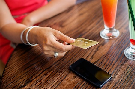 person on phone with credit card - Woman paying with a credit card on a table in a restaurant Stock Photo - Premium Royalty-Free, Code: 6108-06905002