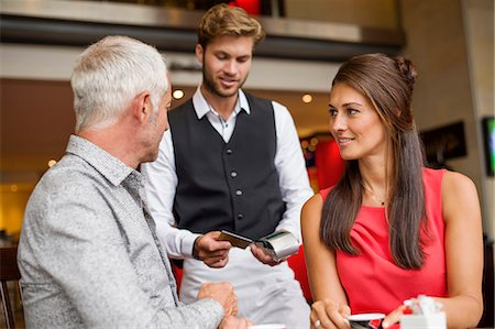 Couple paying with a credit card to a waiter in a restaurant Stock Photo - Premium Royalty-Free, Code: 6108-06905011