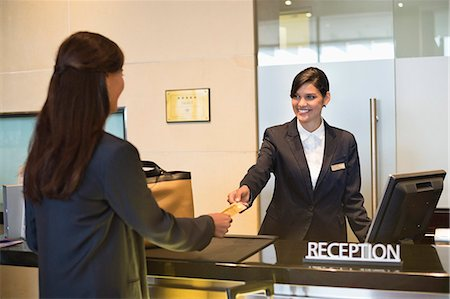 services - Businesswoman paying with a credit card at the hotel reception counter Stock Photo - Premium Royalty-Free, Code: 6108-06905016