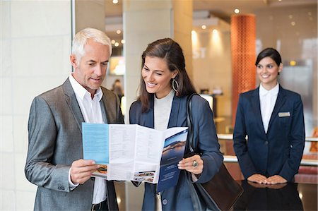 Business couple reading a brochure in front of a hotel reception counter Stock Photo - Premium Royalty-Free, Code: 6108-06905021