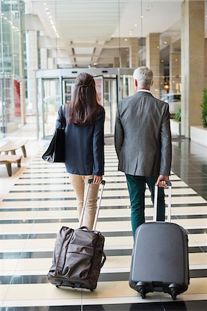 Business couple pulling suitcases in a hotel lobby Stock Photo - Premium Royalty-Free, Code: 6108-06905026